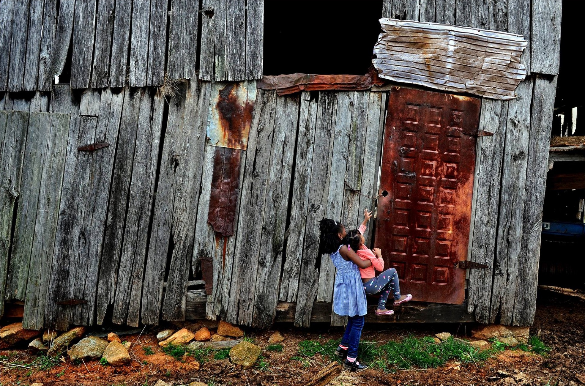 A curious Juliet Pace (age 4) and her cousin Campbell (age 7) got quite a history lesson on Monday as they visited a nearly forgotten slave cemetery where some of their relatives are buried. They also explored a restored slave shack on the grounds of Sweet Briar College (in Amherst, Va.) and this great old barn that belongs to their 75-year-old cousin Jasper. The farm has been in the family since just after the civil war. © 2015 Michael S. Williamson/The Washington Post