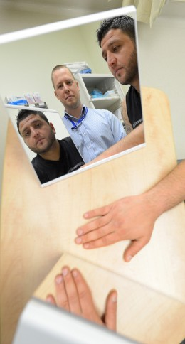 Ashoor Luka used a Mirror Box to cure the chronic pain in his broken wrist with the help of physiotherapist Roland Fletcher (centre). Photo: Boaz Joseph, Surrey Leader.