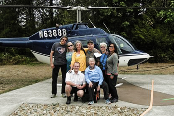 The GSOC field trip group poses with pilot Robert. Left to right are Steve Haar, Cecily Cedilote, Sheila Alfsen, pilot Robert, kneeling, Charles Montross, Anne Oneill, kneeling, Carol Hasenberg, Yumei Wang. Bo Nonn also participated in the trip.