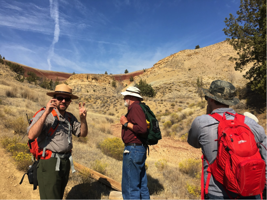 NPS Paleontologist Nick Famoso explains with air quotes and the Clarno Nut Beds in the backdrop. Jon Stroud and Madison Ball are listening. Photo by author.