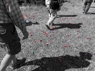 Shotgun shells (in color) littering quarry floor (black-and-white).