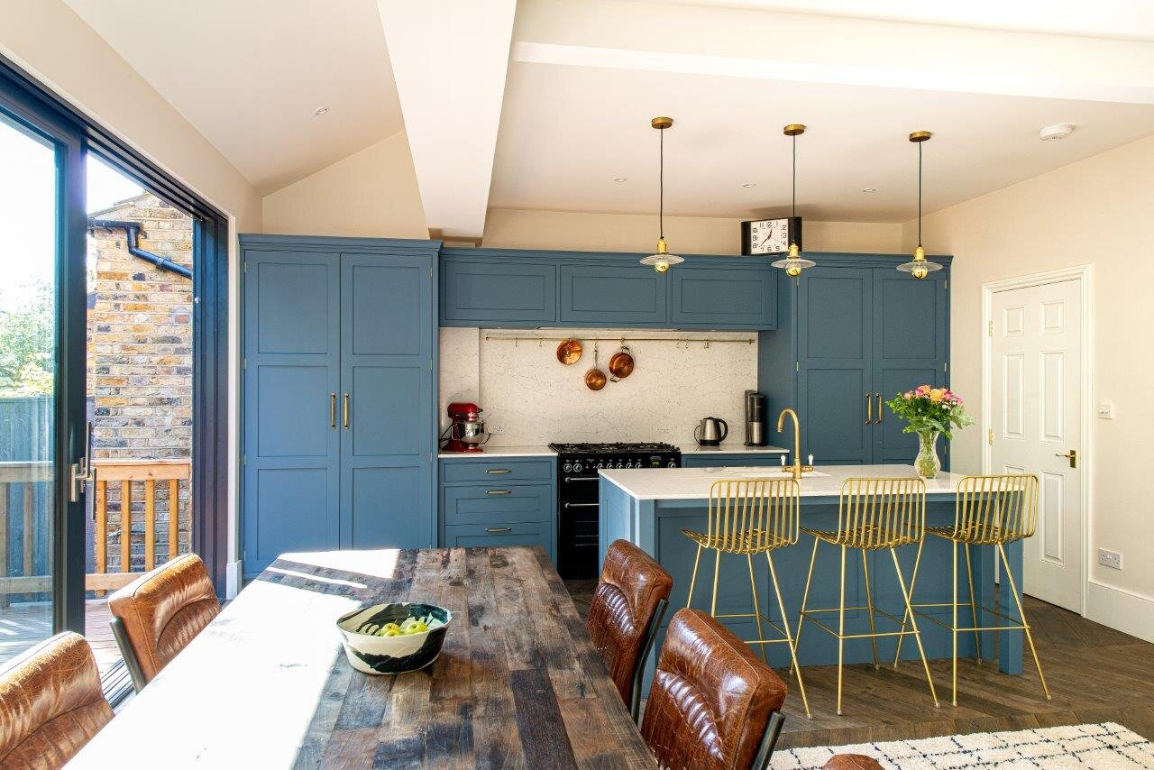 Blue kitchen with brass handles, tap, and chairs and kitchen island.