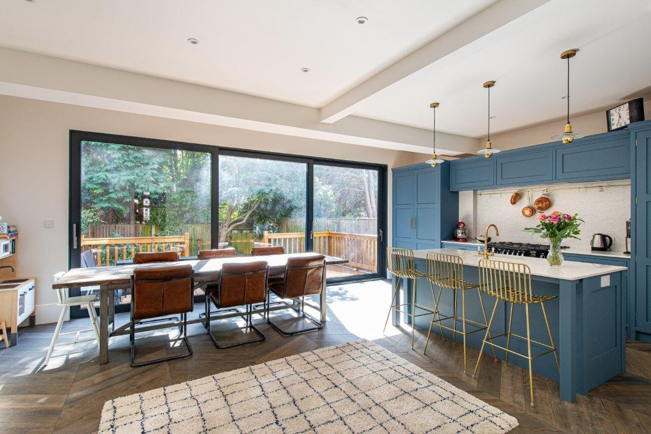 Open plan kitchen and dining room with blue cabinetry and white quartz worktops and splashback.