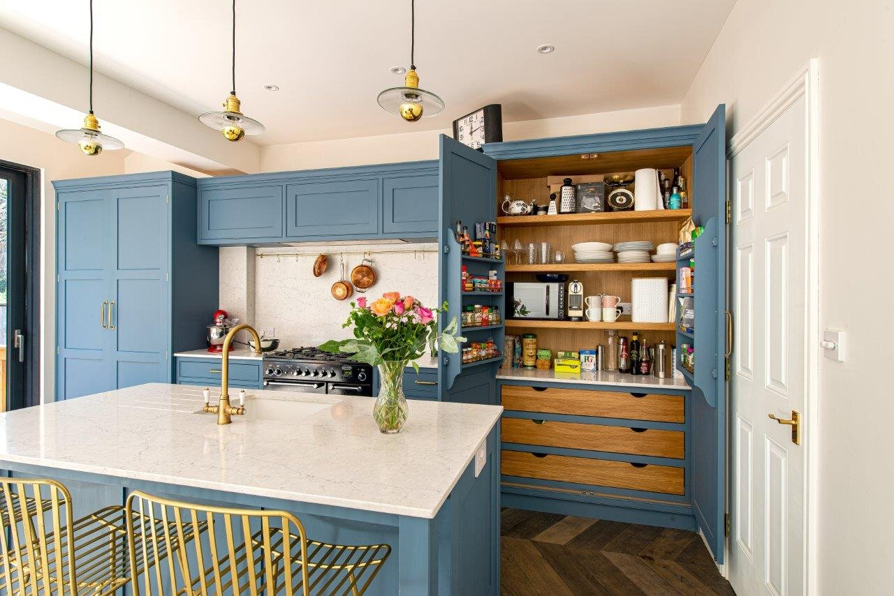 Blue kitchen with quartz worktop and brass handles & tap with large double doored pantry.
