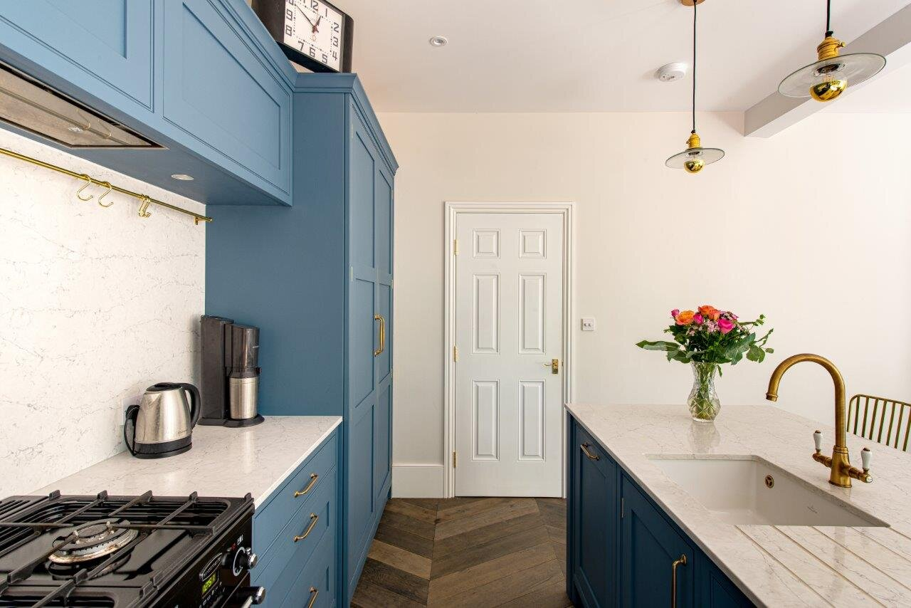Blue kitchen with range cooker, white quartz worktop with engraved draining grooves and brass tap