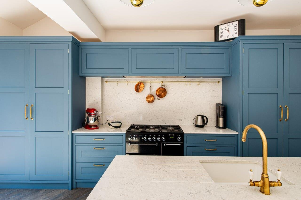 Blue kitchen with brass handles and matching tap.