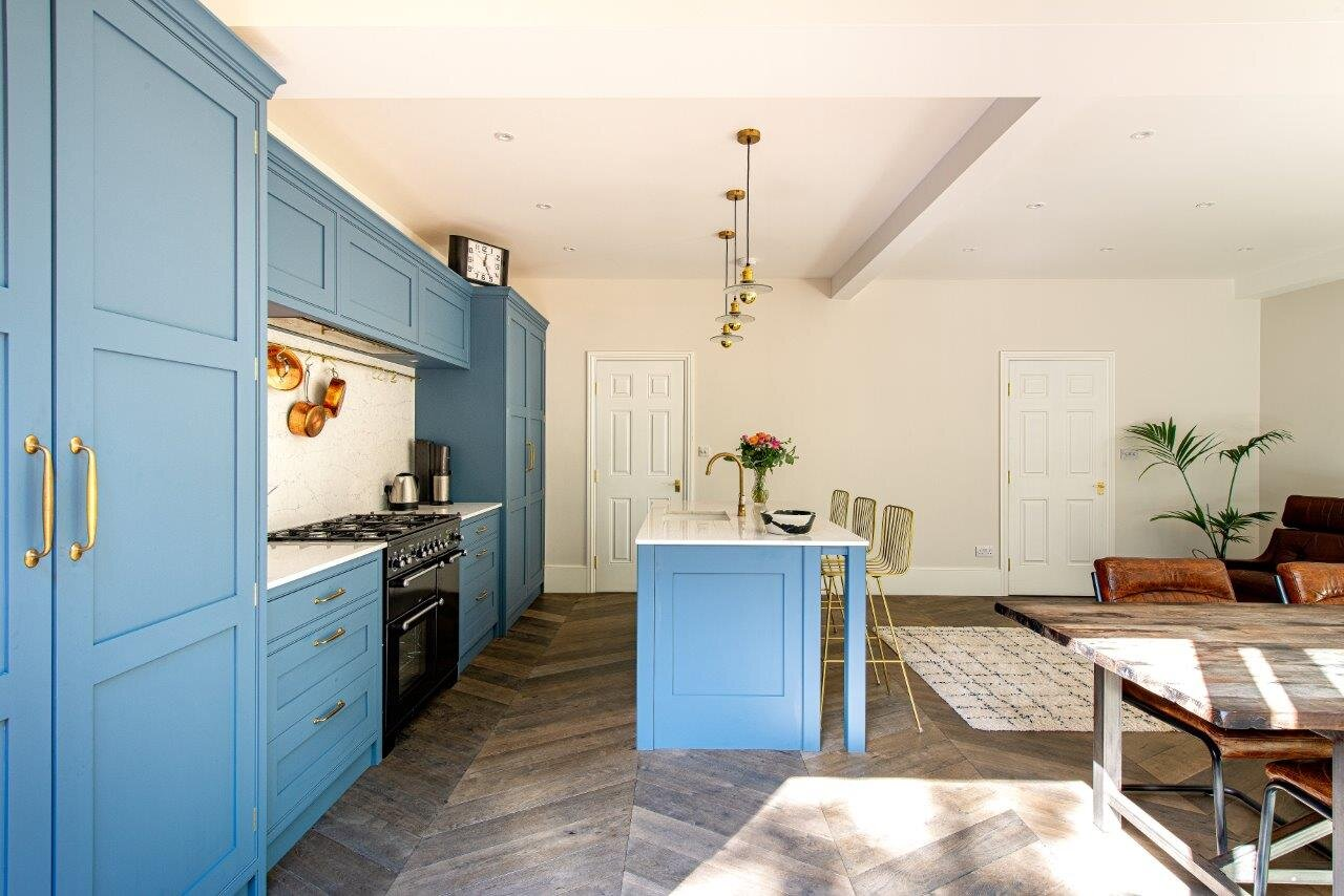 Light blue kitchen with brass handles and tap.