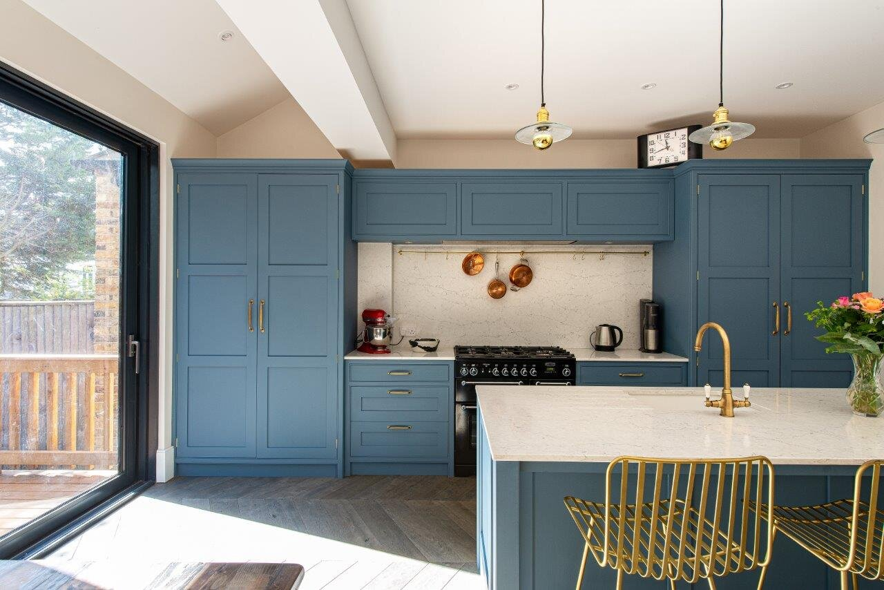 Blue kitchen with integrated fridge and large double door larder.
