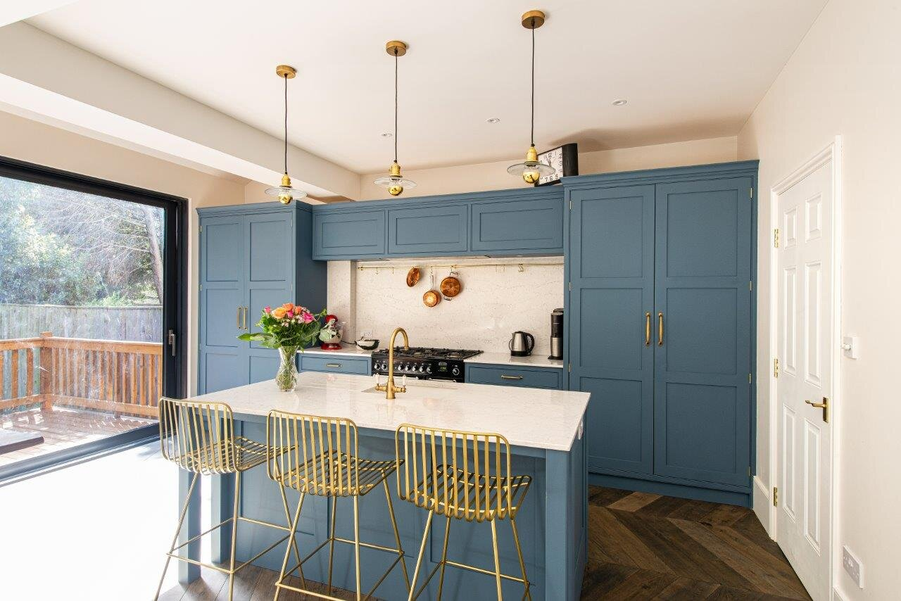 Small, blue kitchen island with light quartz worktop and brass tap