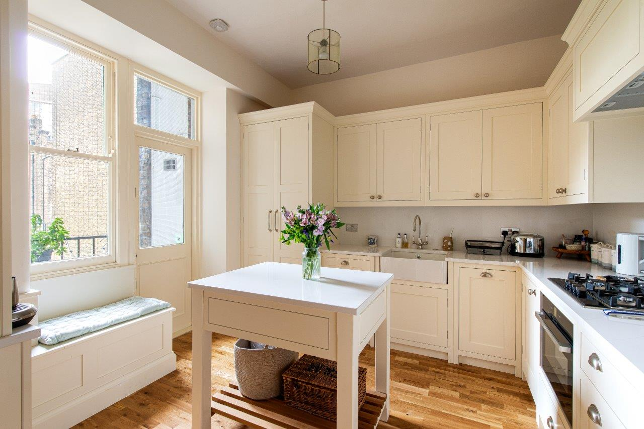 Cream kitchen cabinetry with white quartz worktops, silver handles and tap, single Belfast tap and bespoke bench under window.