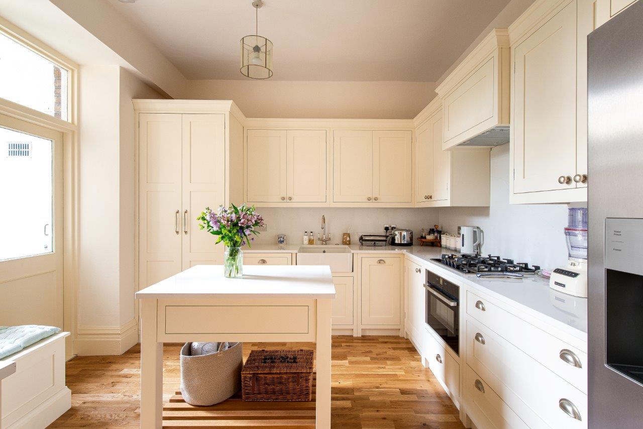 Cream kitchen featuring square chef table with quartz worktop.