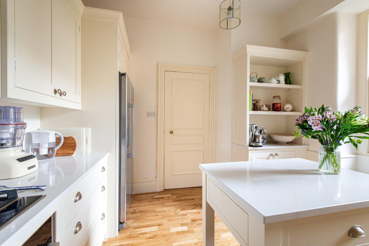 Cream kitchen cabinetry with white quartz worktops, square chefs table and open shelving.