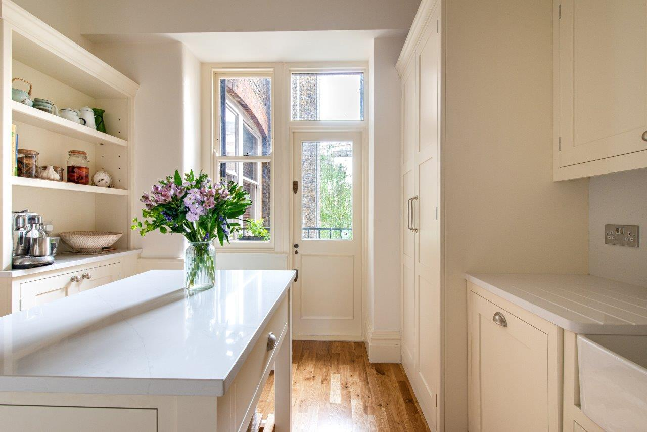 Cream kitchen with open shelving and satin chrome cup handles.