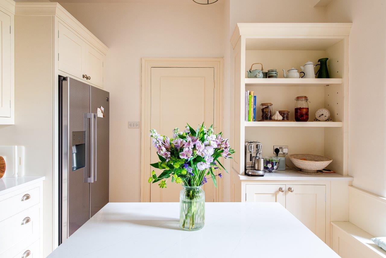 Cream kitchen with open shelving unit and American fridge freezer.