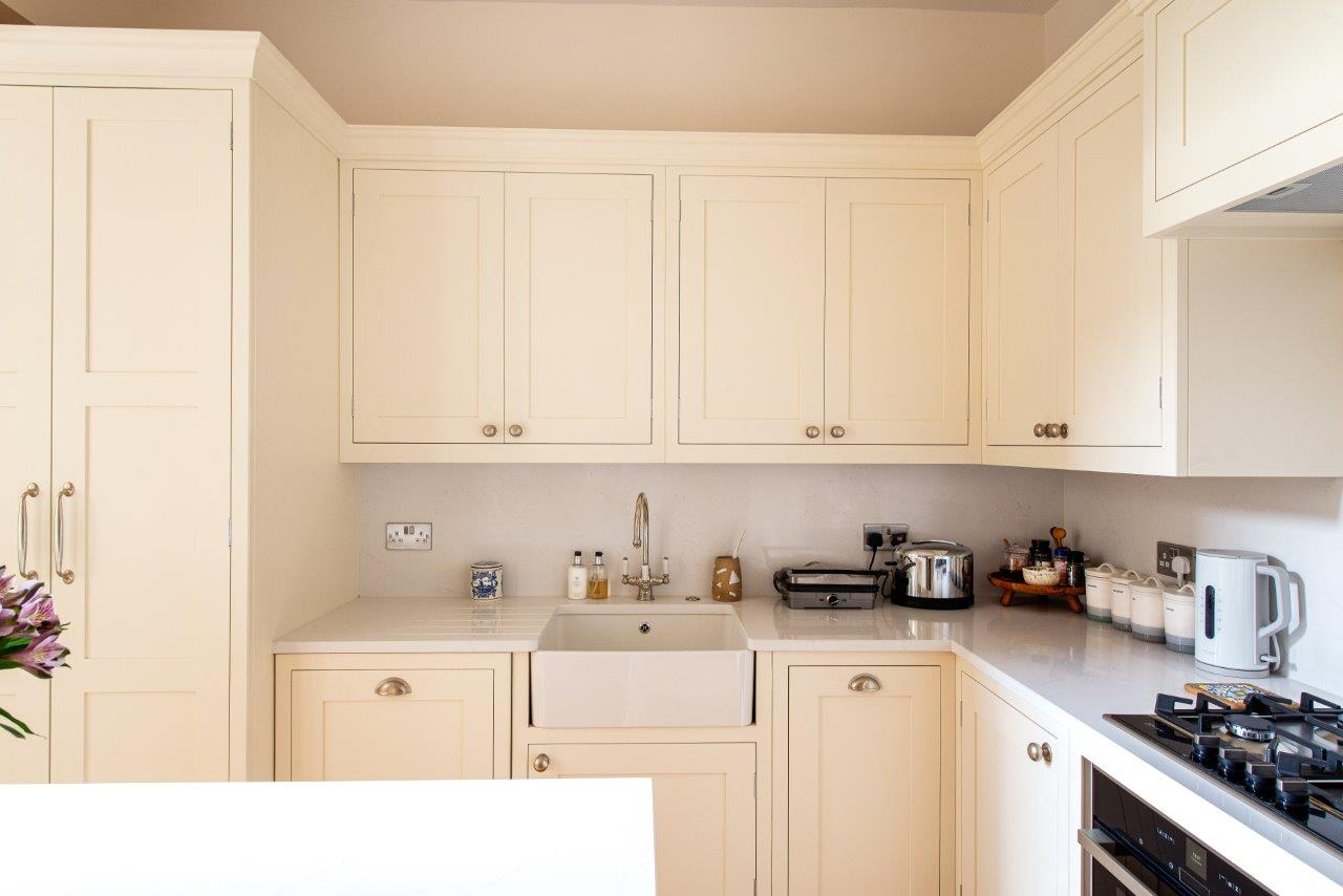 Cream kitchen with single Belfast sink and quartz worktop with draining groves.