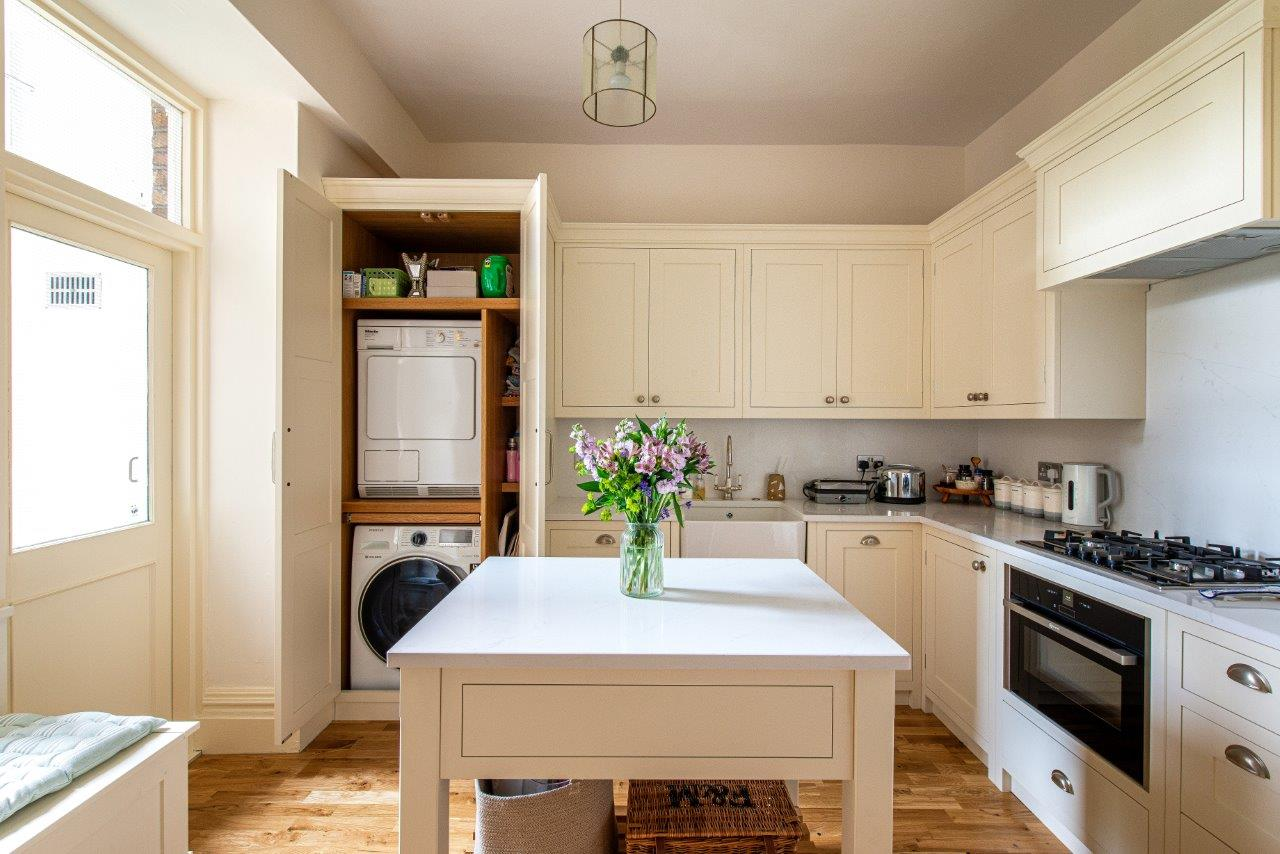 Cabinetry door open revealing bespoke utility space inside.