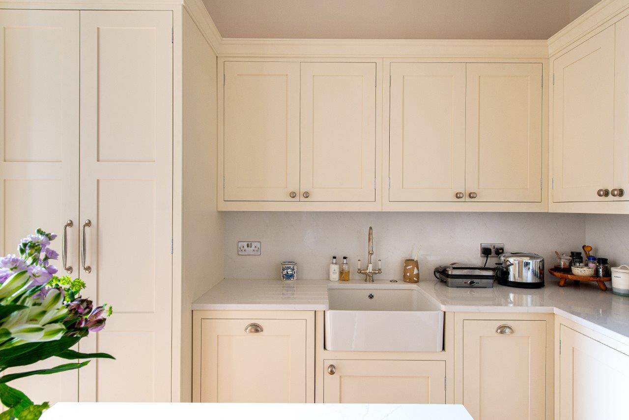 Cream kitchen with brushed chrome handles and a single Belfast sink.