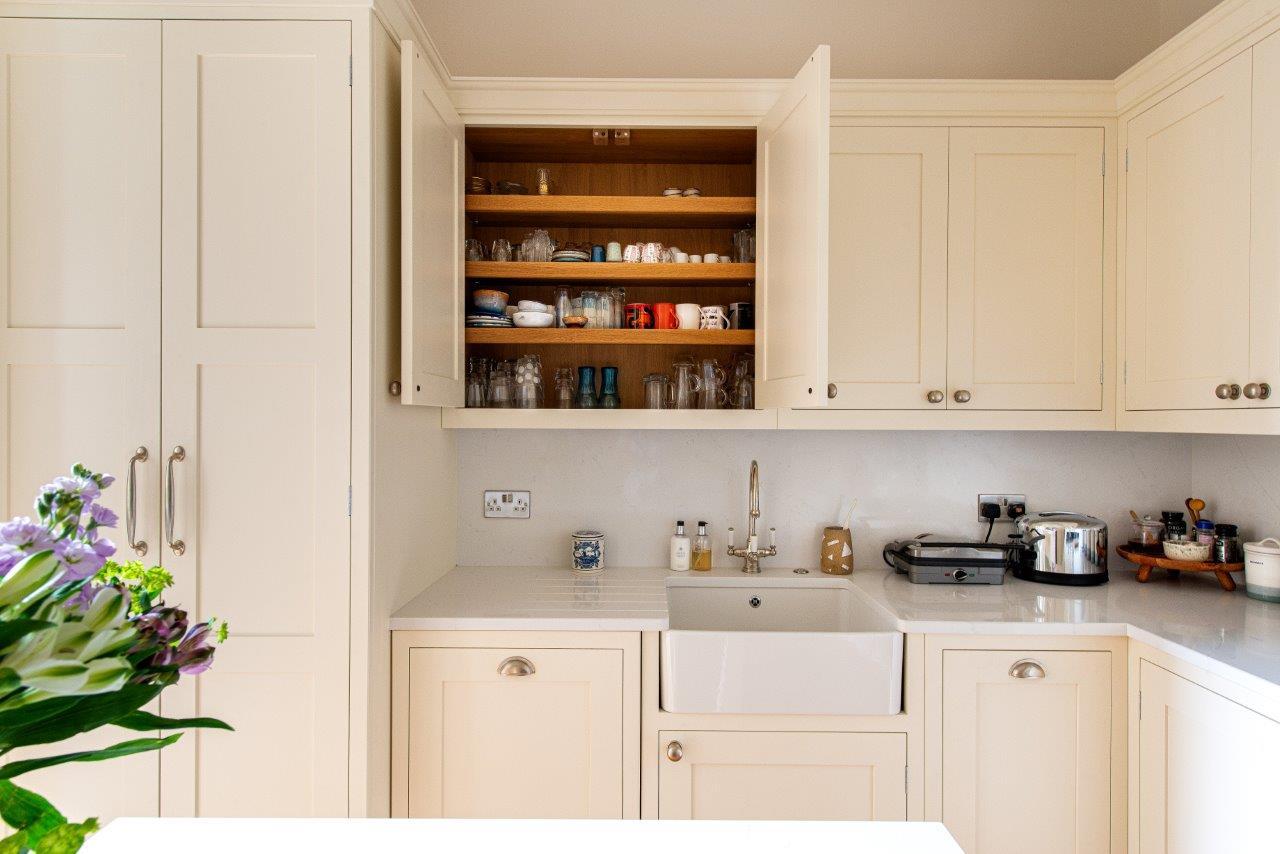 Cream kitchen cabinetry doors open, revealing oak interior.