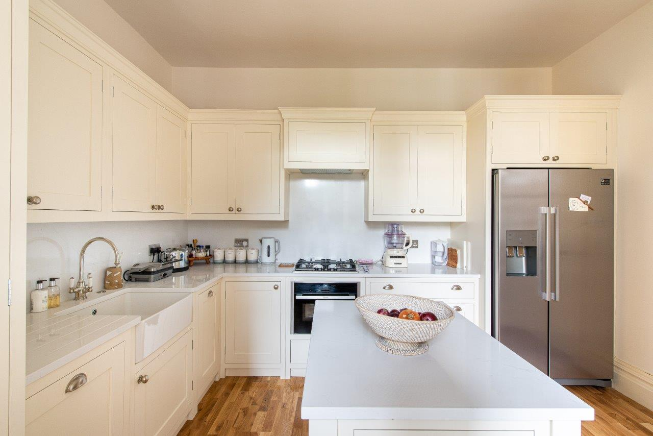 Cream cabinetry with white quartz worktops and silver handles.