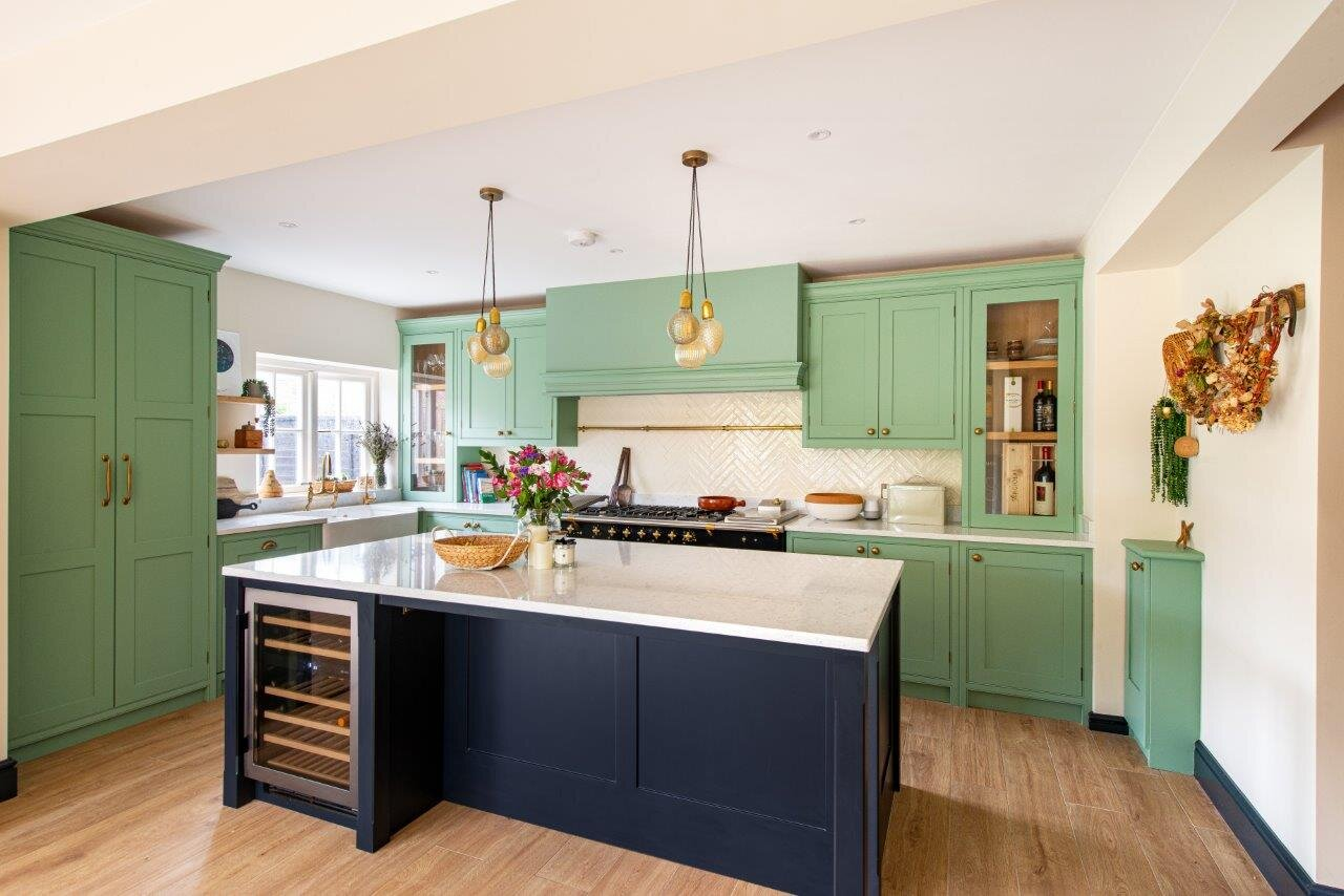 Pale green kitchen cabinetry and black kitchen island with integrated wine cooler fridge.