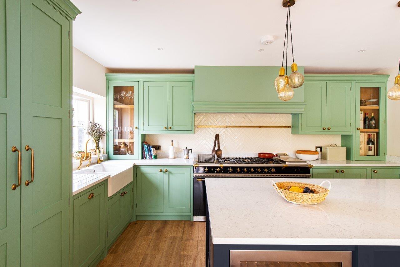 Mint green kitchen, with large range cooker, brass handles and cream tiled splashback