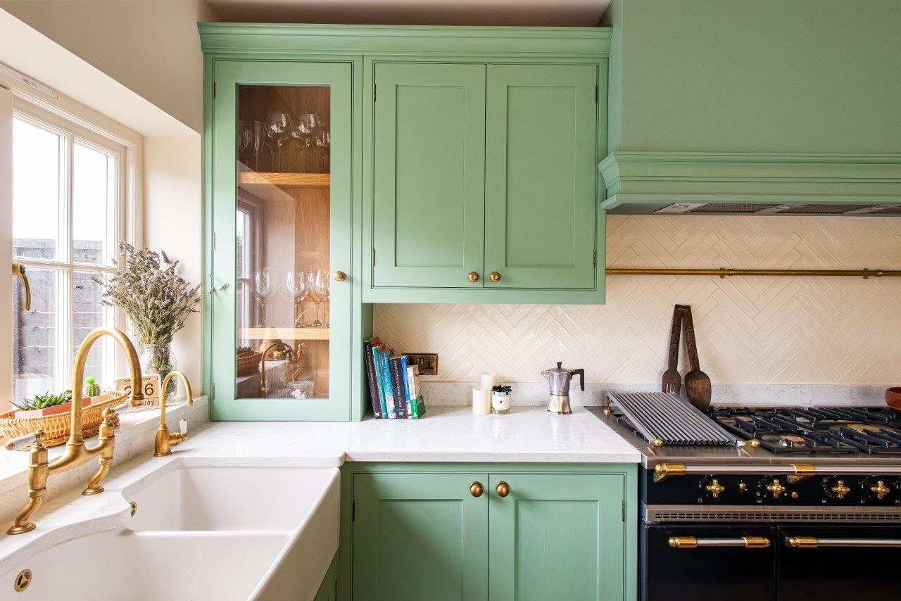 Pale green kitchen cabinetry, with glass unit. White quartz worktops and brass handles & tap