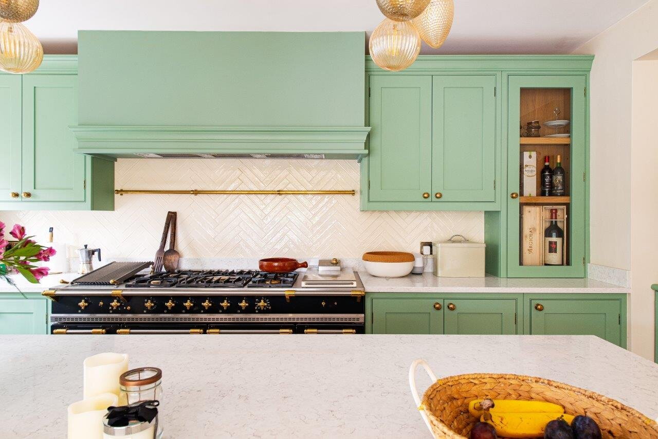 Pale green kitchen cabinetry with round brass knobs, large black range cooker and cream tile splashback.