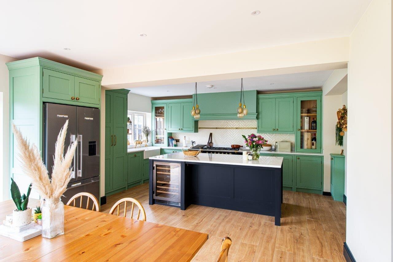 Pale green kitchen cabinetry, black kitchen island with white quartz worktops, brass handles and pendant lights.