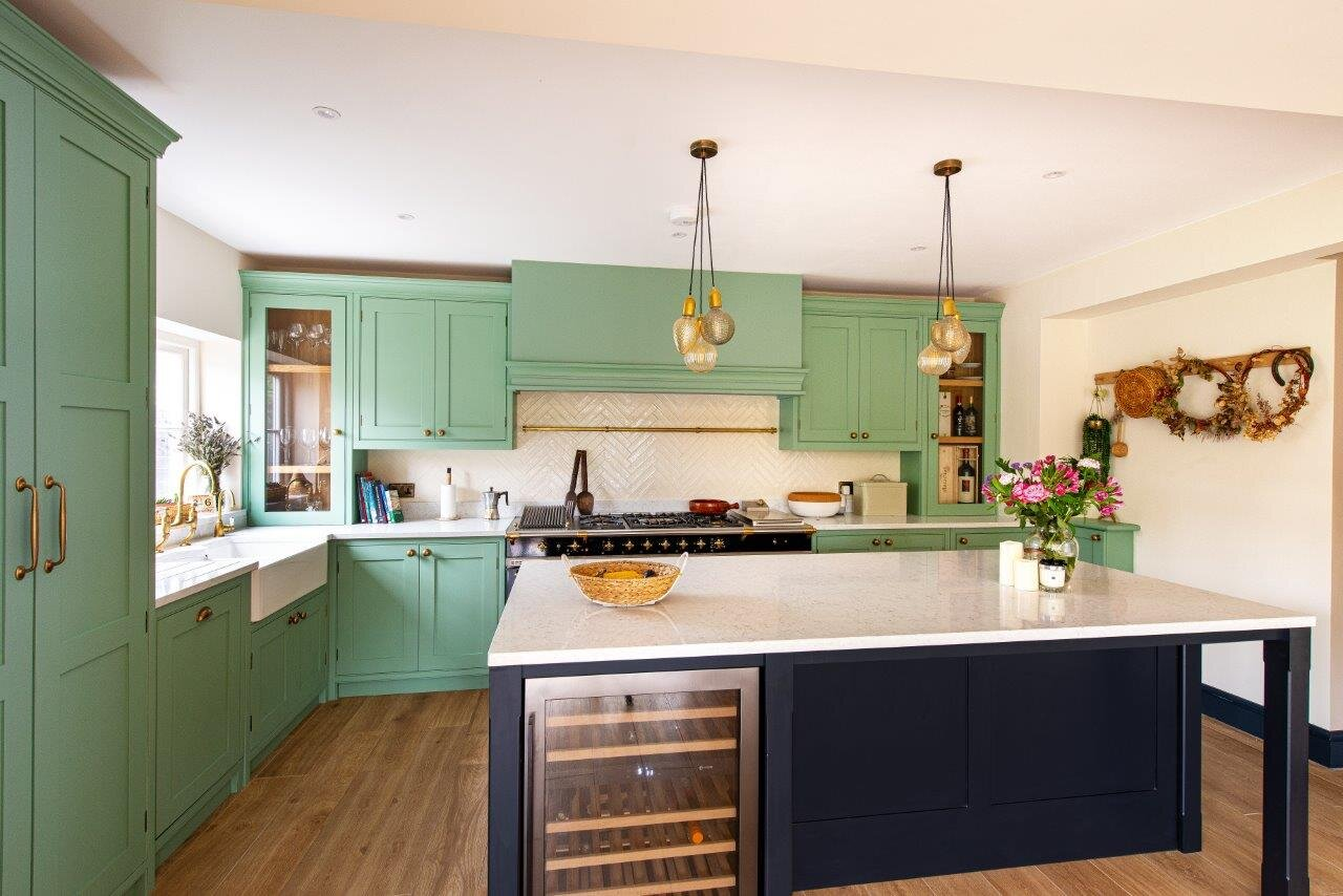 White quartz worktops on pale green kitchen cabinetry and black island.