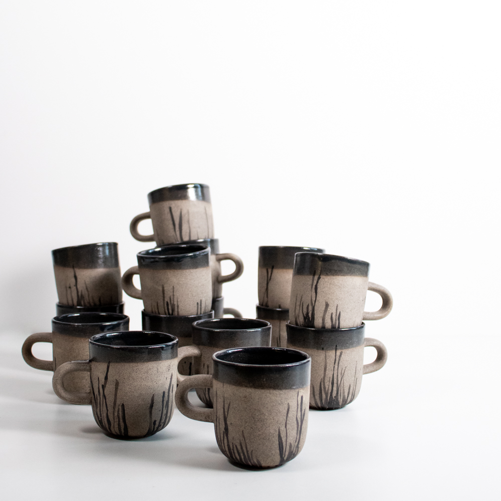 The cups are made from a rough clay and handpainted with ceramic underglaze colour.
