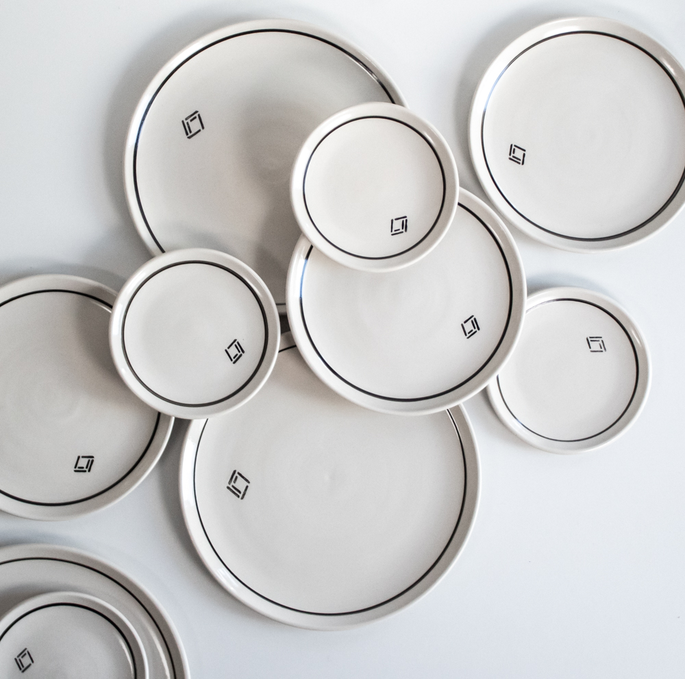 The tableware is made from strong off-white clay, and most of the items have a black stripe near the edge, and a logo stamp.