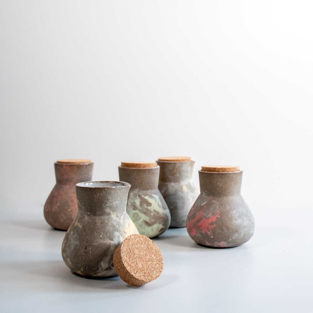 The jugs match the cups with their mixed pastel colours on rough grey clay.
