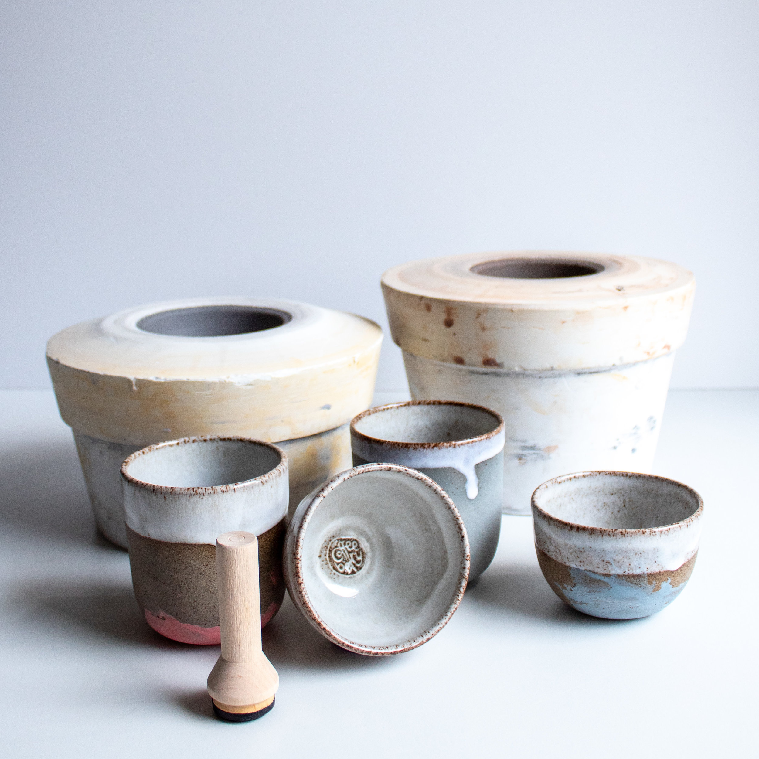 The plaster moulds in the background are used for making the cups.