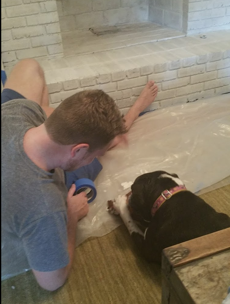 "Weezy ""helping Daddy"" work on the fireplace"