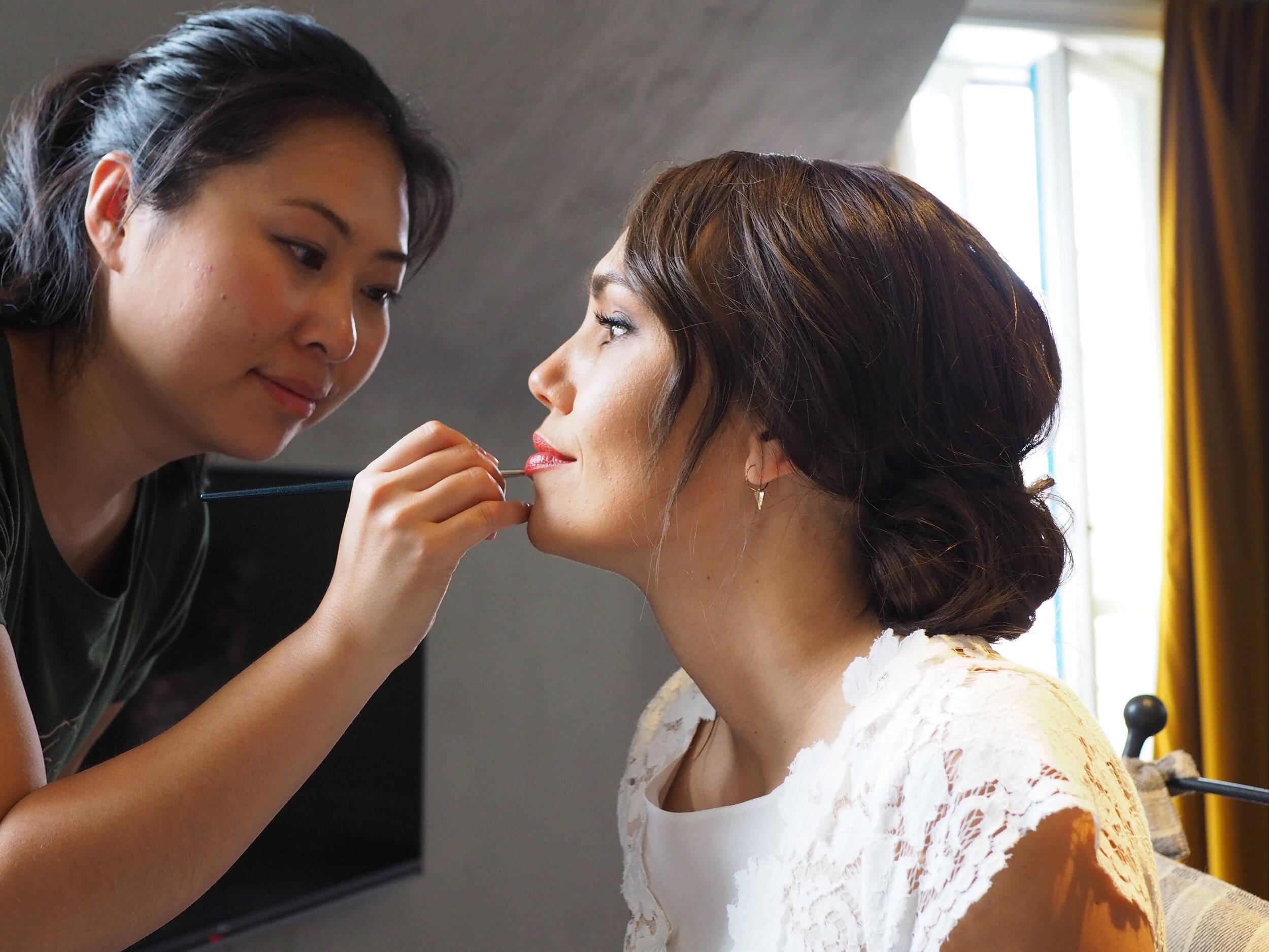 2astylisten och världens bästa Lina (  hitta hennes hemsida här ) lägger på läppar medan jag pysslar i håret på nästa tärna