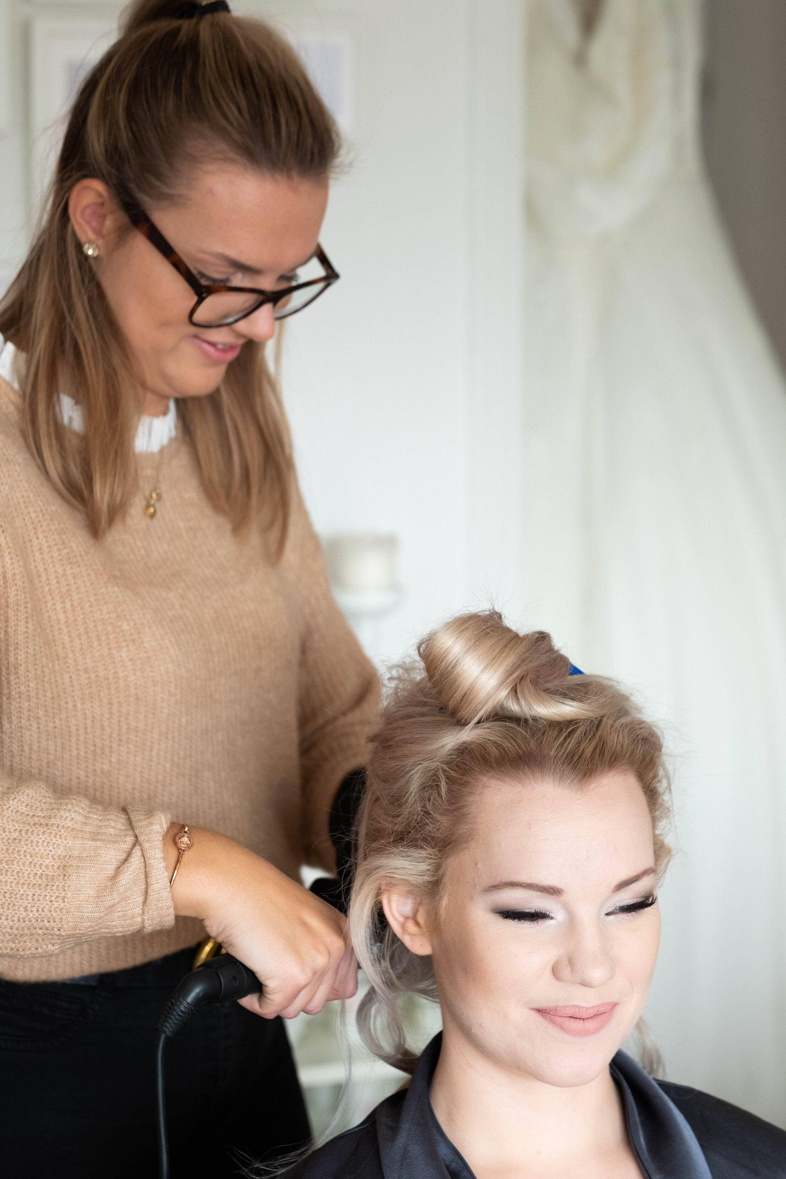 Här pågår hårstyling av brud, frisören Rebecca Johansson fixar lockar i eget hår och löshår till ett högst värdigt hårsvall för dagen