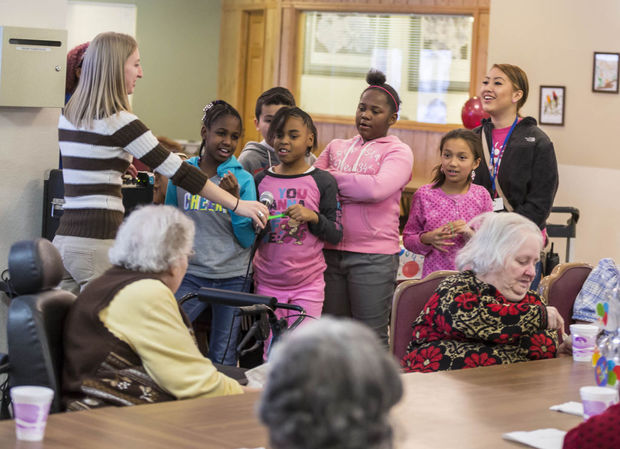 Jill Aronson, left, life entertainment coordinator, leads a group of Leopold Elementary School students in singing happy birthday to residents at Avalon Assisted Living Community.