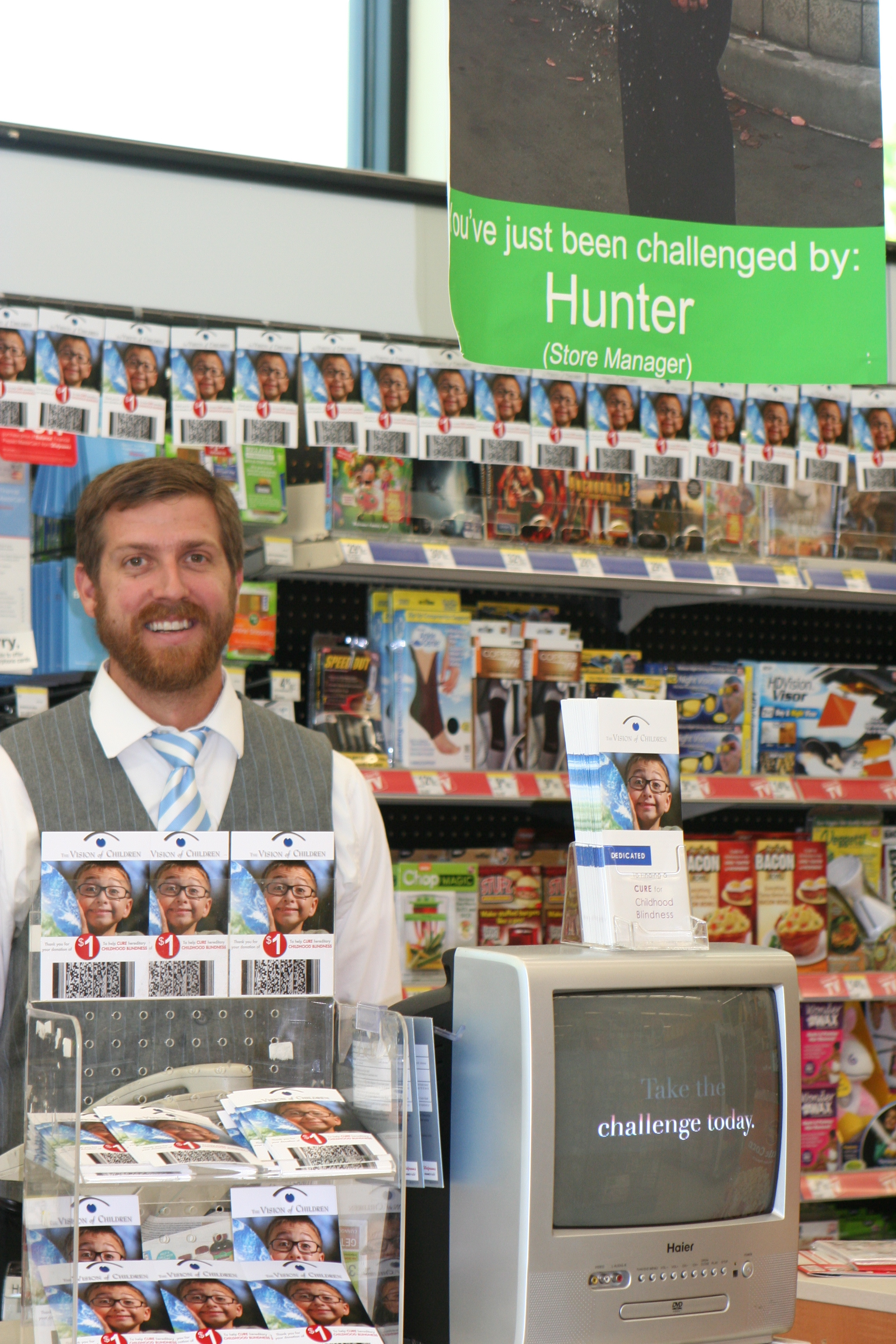Store Manager, Hunter Richmond, stands next to the display of the VOC Challenge video and donate cards.