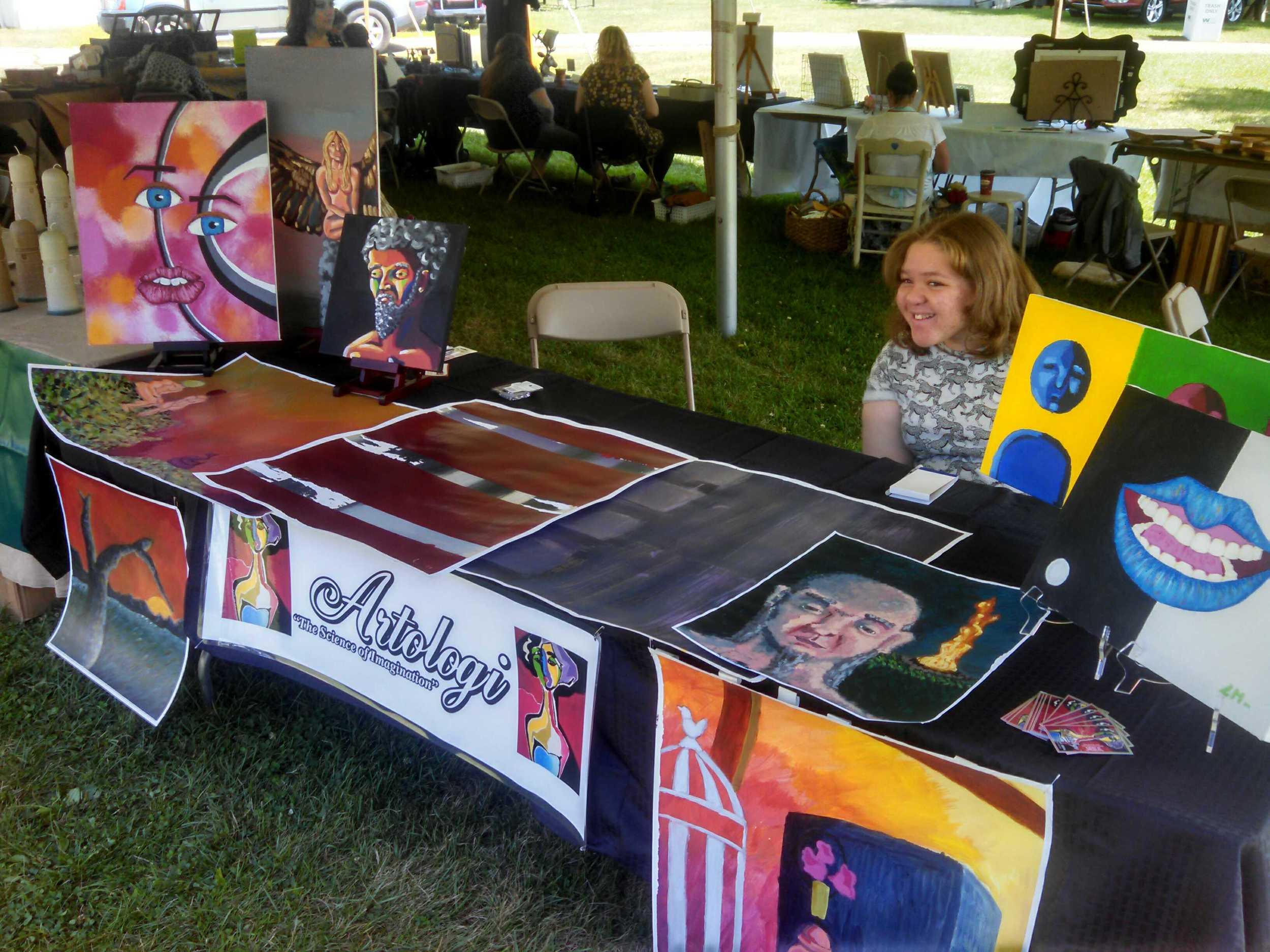 Lauren selling her artwork at a local fair through her business, Artologi.