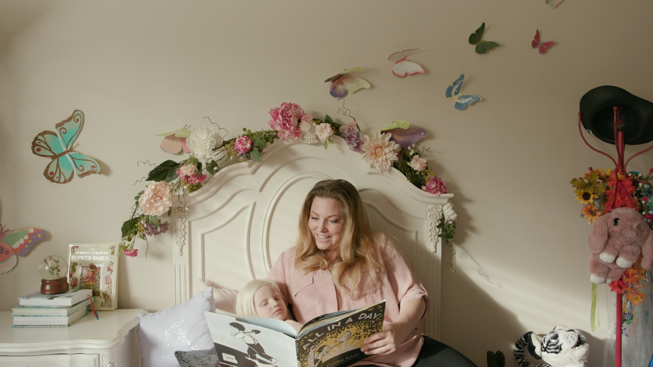 Amanda and her daughter reading together in her daughter's room