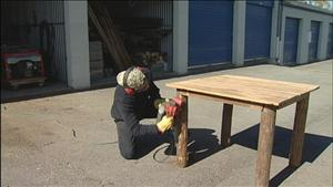Tennessee Barn Wood's owner, Ray Trotta, finishing up some legs to a beautiful signature table.