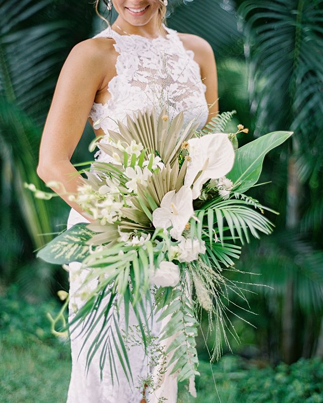 Chariese's cascading tropical bridal bouquet is featured on the front page of @stylemepretty Her bouquet was created with locally foraged foliage (grasses, ferns, and tropical leaves), dried palms, and some focal flowers (anthurium and orchids) that I packed in my luggage😬🌿 Boutonnières and bouquet were wrapped in silk from @tonoandco Image by @spostophoto #destinationwedding #lavendersflowerstravels #sayulitawedding #sayulita #villaamore