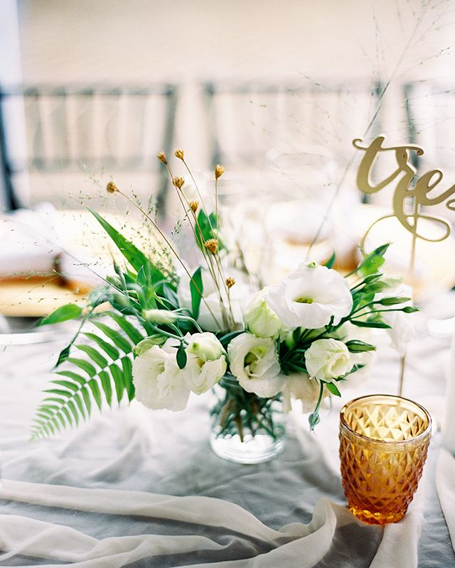 """Chariese and Kevin's Sayulita destination wedding magic is featured on the front page of @stylemepretty Thanks to @spostophoto for capturing it all so well. Sideways tropical rainstorm couldn't stop this reception from happening!✨✨✨The table top arrangements were created with locally foraged foliage, dried floral bits I bought with me in my luggage, and white lisianthus that the Brides family sourced for me. I found """"vases"""" from a local store, which were just simple drinking glasses from the home decor section. We had suitcases filled with votive candles and silk table runners from @tonoandco (totally worth it!). The candles and textiles always pull the table top design together. This destination wedding really was magic✨✨✨ #lavendersflowers #lavendersflowerstravels #sayulita #destinationwedding #villaamore #sayulitawedding"""