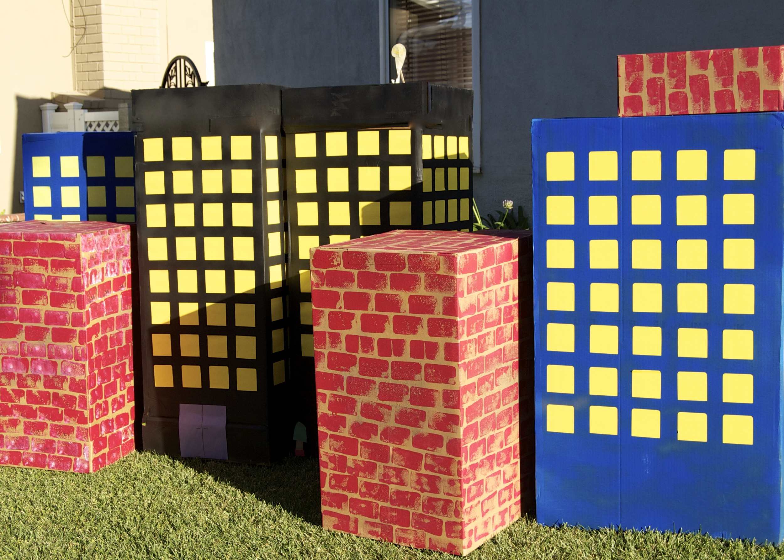 I used spray paint to make the blue and black buildings. These were large, sturdy boxes I found on the side of the road. With a little spray paint and some Post-It Notes, they were transformed for the  Superhero Party .