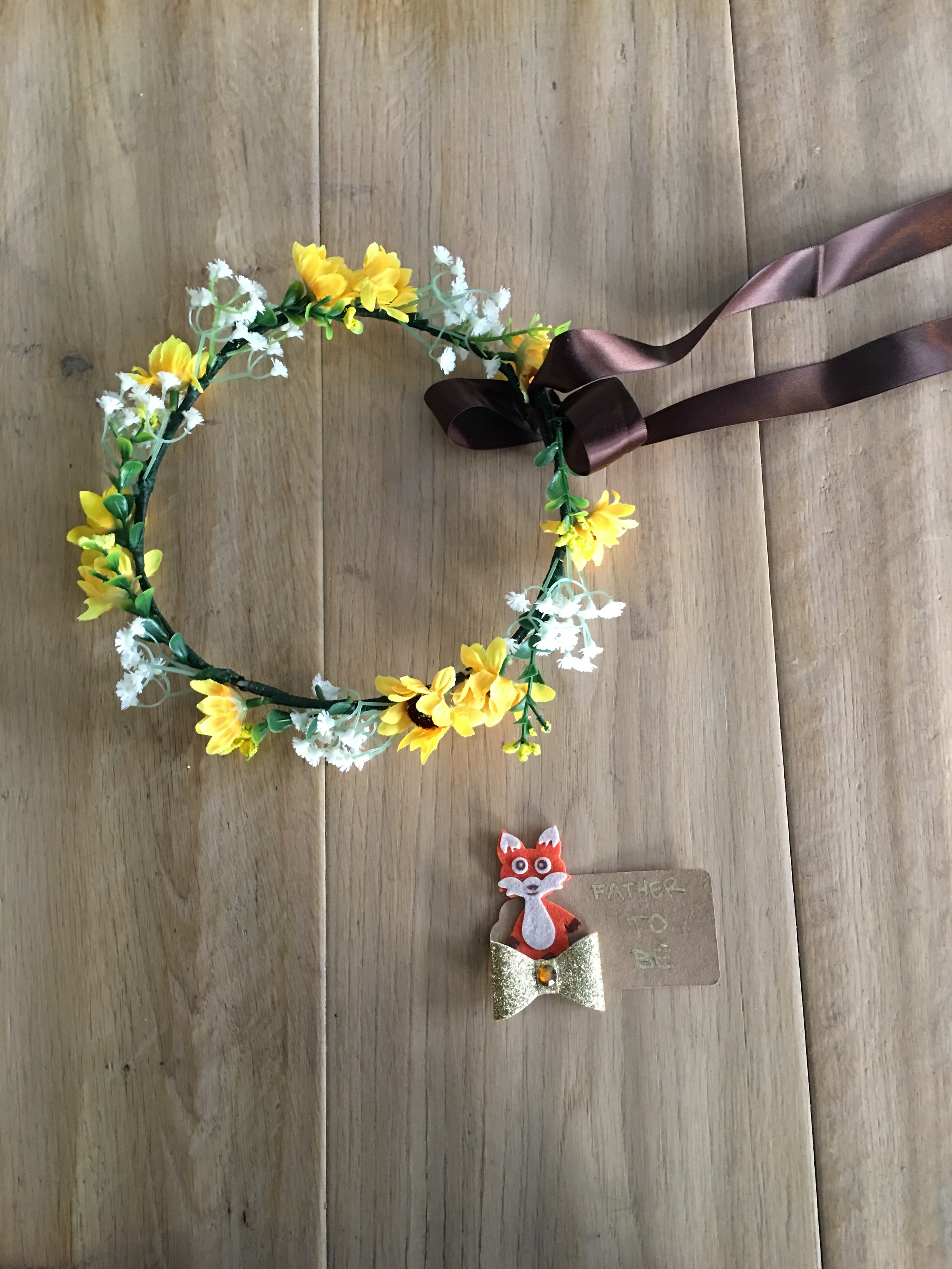 """a floral crown for the mom-to-be. (she loves sunflowers so it went perfectly.) added the long satin brown ribbon for a bit of drama.  Also made a """"Father-to-be"""" pin from a felt sticker, brown paper tag, gold pen, and a bow. Added double sided tape to the back so it can adhere."""