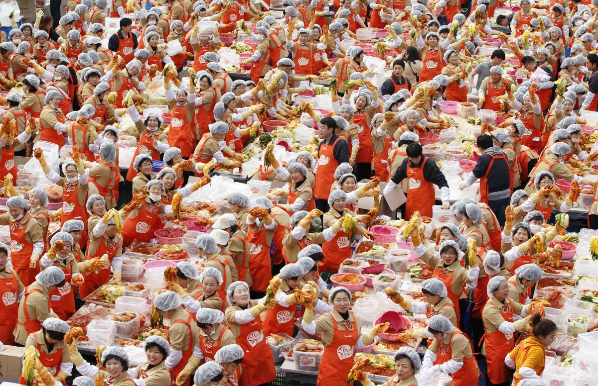 Women pose for the cameras as they make the traditional Korean side dish kimchi, or fermented cabbage, at a charity event at the Seoul City Hall Plaza on November 8, 2011. About 2,000 volunteers made 270 tons of kimchi to give away to needy people during the winter season.
