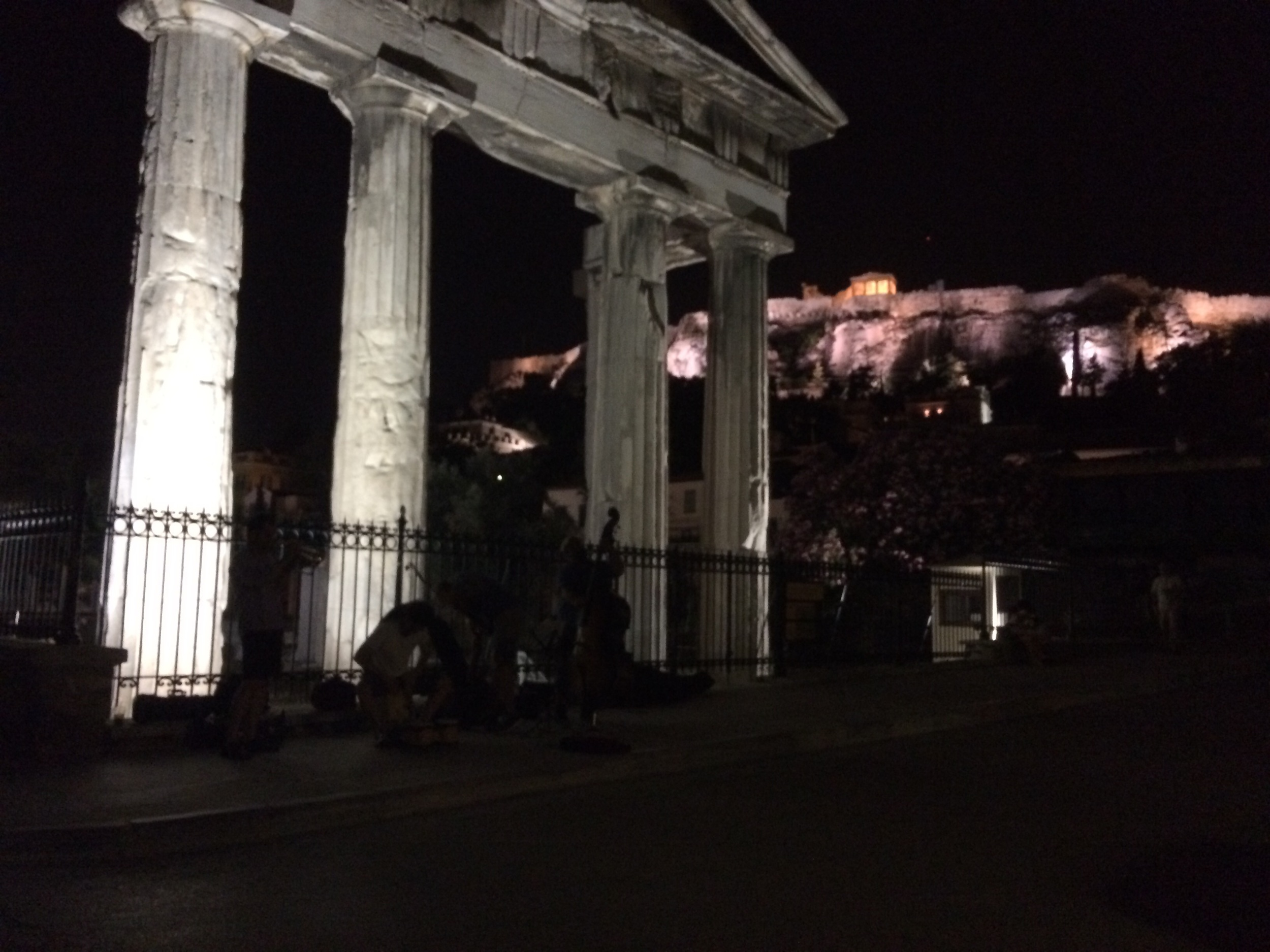 Invisible band in front of random ruins and Acropolis in background