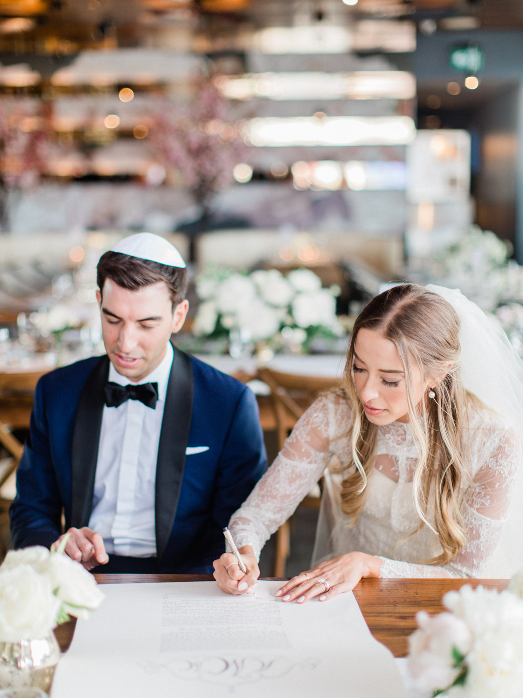 -Bride and groom signing the ketuba at their traditional jewish wedding ceremony at an intimate restaurant venue in Toronto.  Captured by Toronto wedding photographer Corynn Fowler Photography.