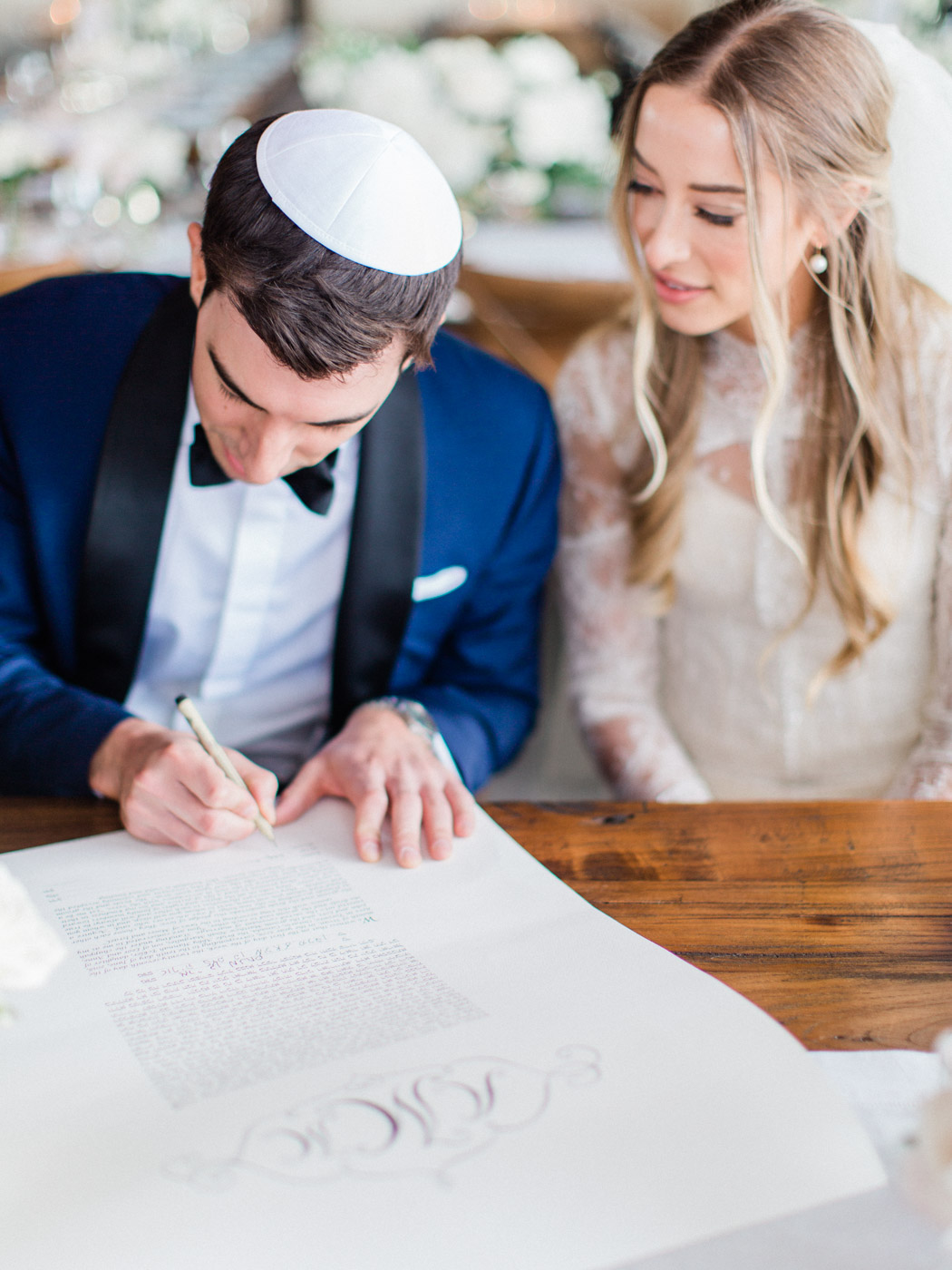 -	Bride and groom signing the ketuba at their traditional jewish wedding ceremony at an intimate restaurant venue in Toronto.  Captured by Toronto wedding photographer Corynn Fowler Photography.