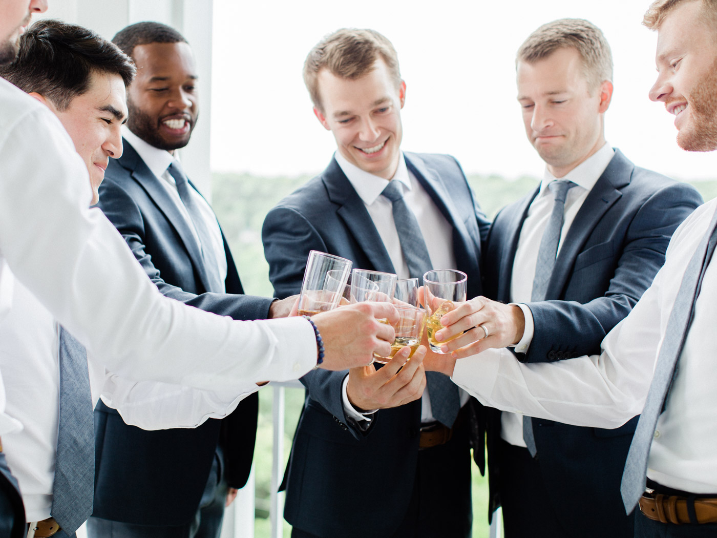 Candid photograph of the groom and groomsmen getting ready for a wedding.  Captured by Muskoka wedding photographer Corynn Fowler Photography.